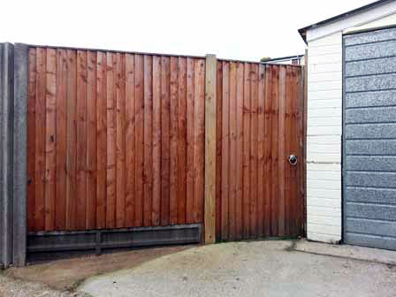 Close board gate + fence on concrete gravel board